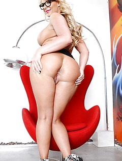 Зрелая грудастая без трусиков позирует в красном кресле