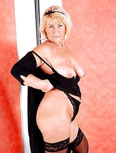 Женщина в возрасте в чулках раздевается догола