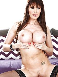 Зрелая грудастая порно модель позирует на кровати
