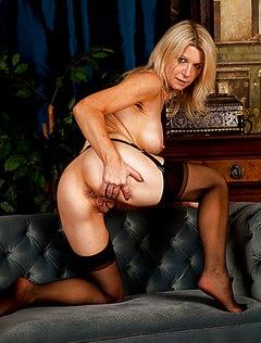 Зрелая блондинка без трусиков позирует в кабинете мужа