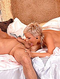 Грудастая блондинка с членом во рту на просторной кровати