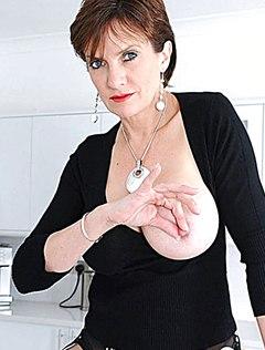 Взрослая озорная жена мнет сиськи на кухонном столе