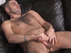 Горячий самец смазывает член перед дрочкой на диване