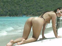 Веселая брюнетка молодая позирует голой на пляже