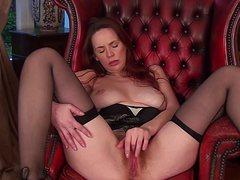 Зрелая женщина рыжая ласкает киску в кресле