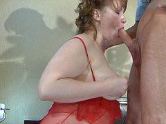 Зрелая женщина в красном пеньюаре ублажает молодой член